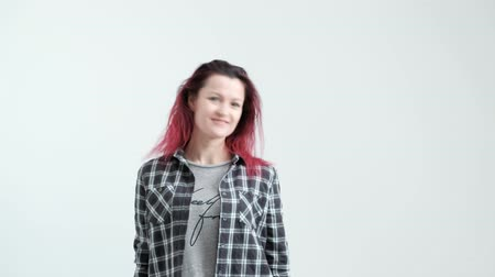 A girl in a checkered gray shirt on a white background with dyed red hair, laughing and smiling.