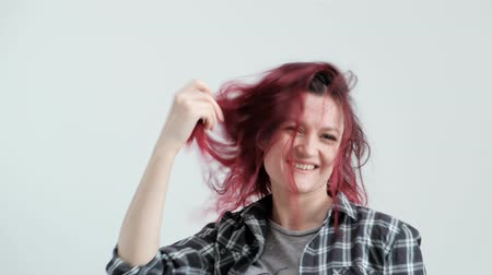 prádelník : A girl in a checkered gray shirt on a white background with dyed red hair, laughing and smiling.