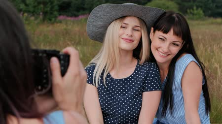 на камеру : Three young attractive girls on a picnic. The photographer takes pictures on the mirrorless camera of two models. Models pose and watch photos. The concept of outdoor recreation. Стоковые видеозаписи
