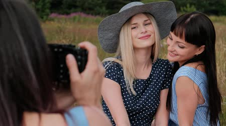 Three young attractive girls on a picnic. The photographer takes pictures on the mirrorless camera of two models. Models pose and watch photos. The concept of outdoor recreation. Wideo