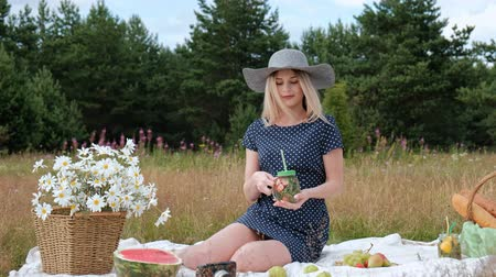 A young beautiful blond woman in a hat and dress is drinking lemonade from a can while sitting on a plaid on the green grass. Picnic basket, a bouquet of daisies, watermelon. The concept of giving away in nature. Wideo