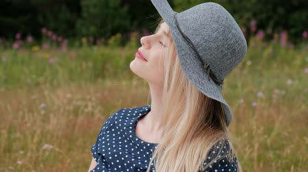 A young attractive blond woman in a blue dress and hat is sitting on a plaid on the grass. The wind blows hair. Picnic in nature.