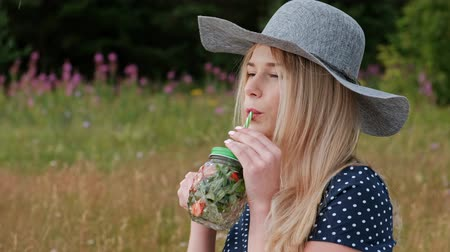 lemoniada : A young beautiful blond woman in a hat and dress is drinking lemonade from a can while sitting on a plaid on the green grass. Picnic basket, a bouquet of daisies, watermelon. The concept of giving away in nature. Wideo