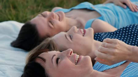 Three young attractive women are lying on a plaid and looking at the sky. Laugh and point up, dance. Rest girlfriends outdoors nature. Picnic concept. Wideo