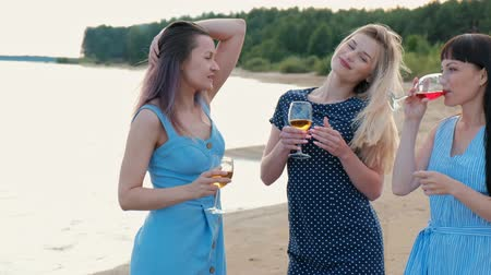 uç : Three young attractive women, in blue dresses are walking along the seashore. Girlfriends communicate, laugh and drink wine. Outdoor recreation. Stok Video