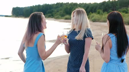 Three young attractive women, in blue dresses are walking along the seashore. Girlfriends communicate, laugh and drink wine. Outdoor recreation. Wideo