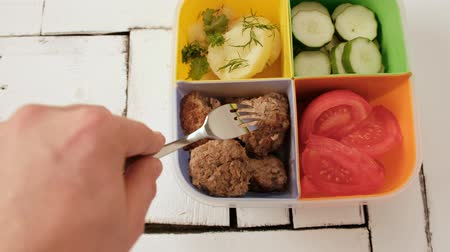 İsveççe : Lunch box with cells. vegetables, cucumbers and tomatoes, boiled potatoes and meat patties. The concept of lunch at work or school. Stok Video