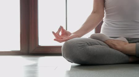 position du lotus : Close-up, a woman is sitting on the floor in the lotus position. Home exercises in yoga. Against the background of a large window in the room. Vidéos Libres De Droits