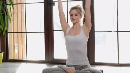 благополучия : A young beautiful athletic woman blonde sits on the floor and breathes her arms folded across her chest. Yoga exercises at home.