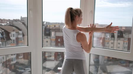 yoğunlaşma : Young beautiful athletic woman blonde in white sportswear doing yoga and stretching on the balcony at home. Stands on the fingers and performs dance steps. Concept of home sport and active lifestyle. Stok Video