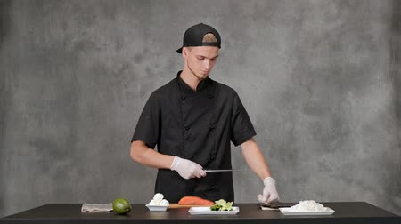 kaviár : Young man chef cook in black clothes on a gray background. Kitchen table, ingredients for Japanese sushi and rolls. The cuisine of the restaurant. Stock mozgókép