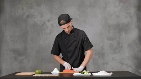 нарезки : Young man chef cook in black clothes on a gray background. Kitchen table, ingredients for Japanese sushi and rolls. The cuisine of the restaurant. Стоковые видеозаписи