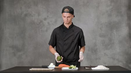 готовка : Young man chef cook in black clothes on a gray background. Kitchen table, ingredients for Japanese sushi and rolls. The cuisine of the restaurant. Стоковые видеозаписи