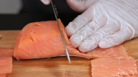 fumado : A young male sushi chef cuts a smoked salmon filet with a knife on a table. Hands in gloves close-up, gray background. Vídeos
