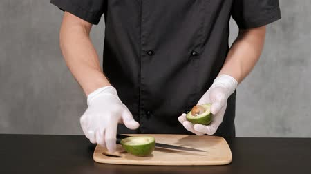 handheld shot : Young chef man in black clothes on a gray background peels, avocado with a knife. Close-up of hands.