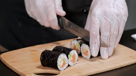 ノリ : Young male sushi chef prepares Japanese sushi rolls of rice, salmon, avocado and nori. Restaurant kitchen, closeup hands cut a roll with a knife.