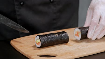 нори : Young male sushi chef prepares Japanese sushi rolls of rice, salmon, avocado and nori. Restaurant kitchen, closeup hands cut a roll with a knife.