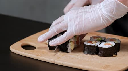 potraviny : Young male sushi chef prepares Japanese sushi rolls of rice, salmon, avocado and nori. Restaurant kitchen, closeup hands cut a roll with a knife.