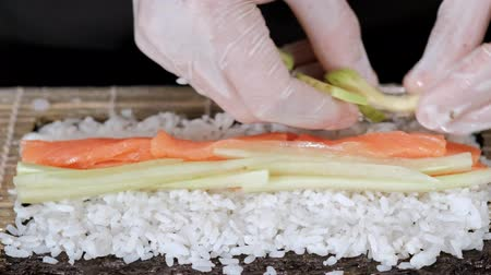 potraviny : Young male sushi chef prepares Japanese sushi rolls of rice, salmon, avocado and nori. Restaurant kitchen, hands closeup.