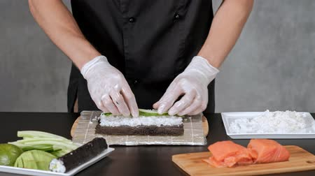 нигири : Young male sushi chef prepares Japanese sushi rolls of rice, salmon, avocado and nori. Restaurant kitchen, hands closeup.
