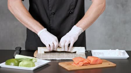 васаби : Young male sushi chef prepares Japanese sushi rolls of rice, salmon, avocado and nori. Restaurant kitchen, hands closeup.