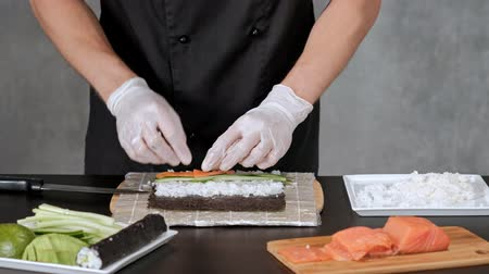 нори : Young male sushi chef prepares Japanese sushi rolls of rice, salmon, avocado and nori. Restaurant kitchen, hands closeup.