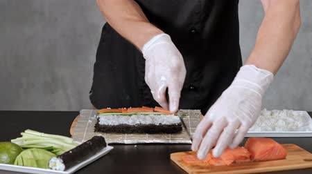 ノリ : Young male sushi chef prepares Japanese sushi rolls of rice, salmon, avocado and nori. Restaurant kitchen, hands closeup.
