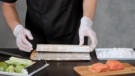 нори : Young male sushi chef prepares Japanese sushi rolls of rice, salmon, avocado and nori. Restaurant kitchen, hands closeup, rolls on mat.