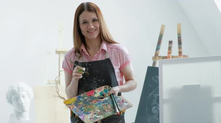芸術家 : Young beautiful woman painter among easels and canvases in a bright studio. Inspiration and hobby. 動画素材