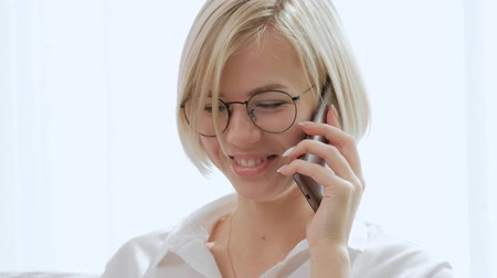 teknolojileri : A young beautiful blond woman with short hair wearing glasses is talking on a mobile phone while sitting on a sofa in a bright apartment. Office life, businesswoman.