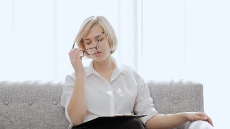çeken : A young beautiful blond woman with short hair with glasses sits on a sofa in a light apartment. Tired of work, sore neck and back, migraine. Office life, businesswoman.