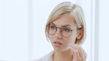 models : Young beautiful woman blonde with short hair in glasses on a white background. Clever and elegant, rejoices at the victory and carefully looks. Office life, businesswoman. Stock Footage