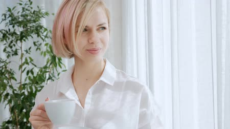 longhair : A young beautiful blond woman with short hair with glasses drinks coffee from a white cup in a light apartment. Office life, break, rest and relaxation. Stock Footage