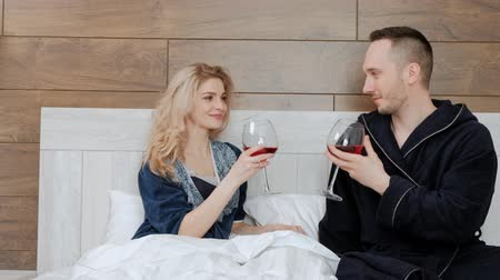 Young married couple in bathrobes drinking red wine lying on a white bed in the bedroom in the hotel room. Celebrate honeymoon or wedding anniversary.