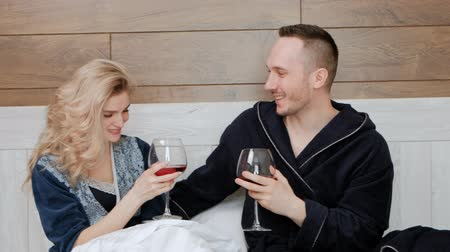 reclináveis : Young married couple in bathrobes drinking red wine lying on a white bed in the bedroom in the hotel room. Celebrate honeymoon or wedding anniversary.