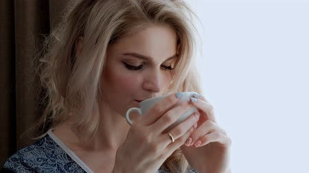 pletený : A young beautiful blond woman in a blue robe stands by the window of a room and drinks tea or coffee from a white cup. Smiles and gets pleasure.