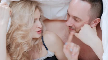 пробуждение : A young married couple, a man and a woman are lying on a bed with white linens. Morning and awakening. Having fun and smiling.