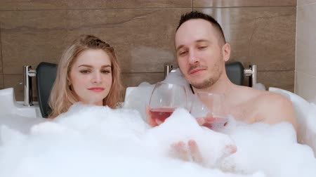 bubbles soap : Young couple, man and woman, lie in the bath with foam. Relax in the hotel. Drink red wine.