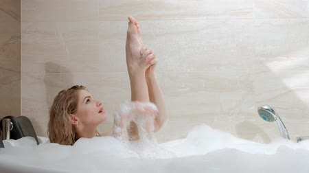 bańki mydlane : Beautiful young woman blonde lies in the bath tub with foam. Resting and relaxing. Spa and exfoliating treatments at the hotel.