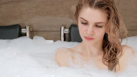 mentiras : Beautiful young woman blonde lies in the bath tub with foam. Resting and relaxing. Spa and exfoliating treatments at the hotel.