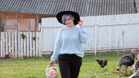 chicken coop : Young beautiful woman farmer in a sweater and a black hat with a brim against a background of green grass and a coonhouse. Holds a basket of chicken eggs.