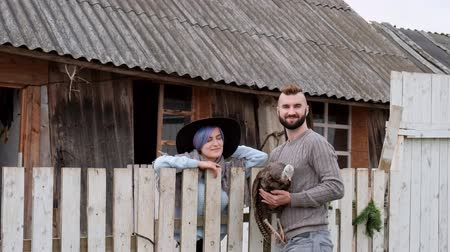 kuşçuluk : Young beautiful man and woman, married couple, in a village on a farm, with a turkey in their hands. Family farming business.