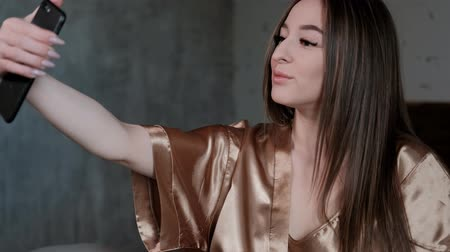 выражающий : Young beautiful brunette woman lying on the bed in a golden robe. Makes a selfie smartphone.