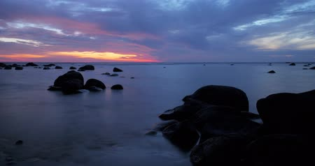 rocks red : Sunset time lapse of clouds over a gentle tide on a rocky shore Stock Footage