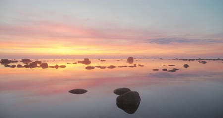 slowing : Time lapse of the last light of sunset behind clouds which slow down in a pink, yellow and blue sky above a still sea with large rocks