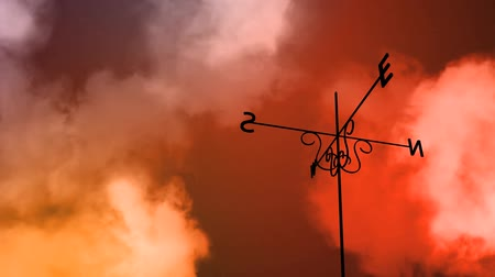 направление : High definition animated loop of a weather vane blowing in the wind. As the clouds take a stormy turn midway through the vane switches direction completely.