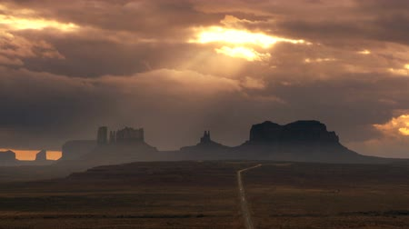 údolí : Fast moving clouds with sun shining through illuminating a panorama of sandstone rock formations in Monument Valley