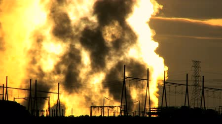 climate : Steam from desert energy production plant pumping into the atmosphere at sunrise beside electricity pylons Stock Footage
