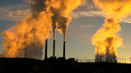 çevre : Smoke from three power station chimneys colored gold from the rising sun polluting the environment Stok Video