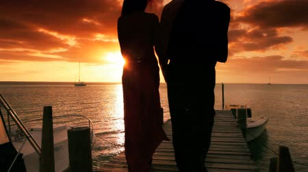 paraíso : Couple in evening clothes on a wooden jetty watching the sunset